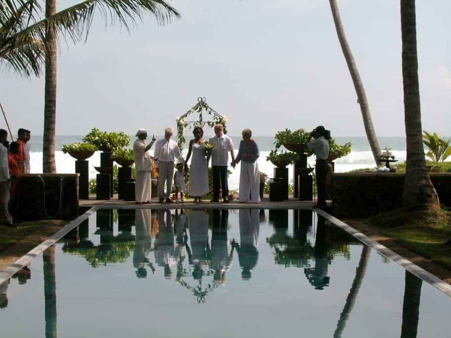 Wedding Ceremony at Apa Villa - the couple with witnesses stand in front of a swimming pool with the ocean and palm trees behind them