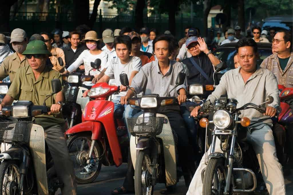 Vietnamese locals in Hanoi on motorbikes at a junction ready to start their engines