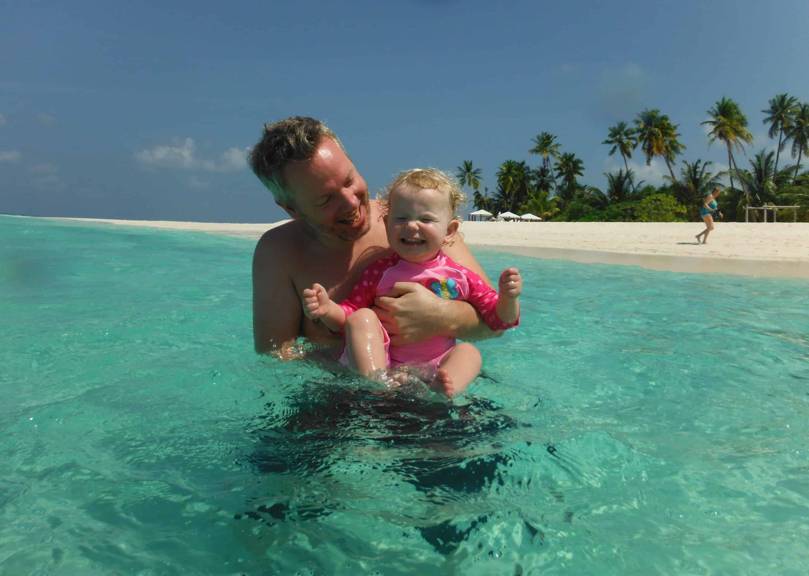 Young child and father in the turquoise sea on a family holiday to the Maldives