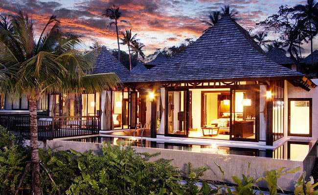 Pool villa at Vijitt Phuket. Lights are on in the villas and palm trees and foliage in the garden.