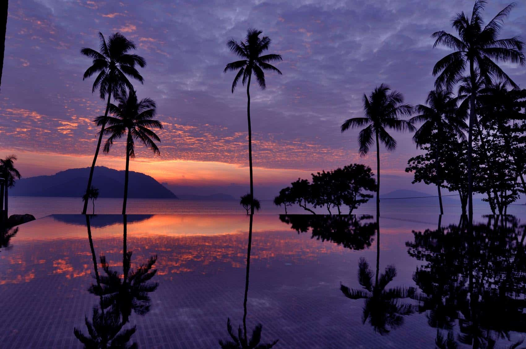 Sunset above the swimming pool at Vijitt Resort Phuket with palm trees and islands in the distance