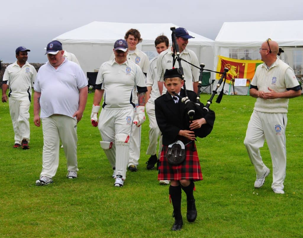 Dr. Lilantha Wedisinghe from the Sri Lanka Association and his team are lead on to the field by a Scottish piper.