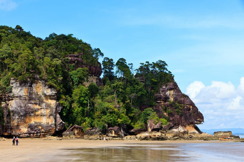 Coastal landscape of Bako National Park with beach in the foreground and forests, rocks and hills in the background