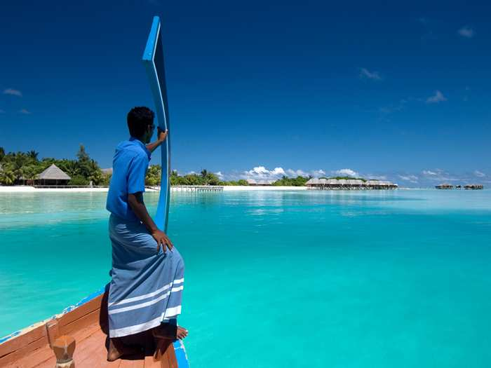 A local steering a dhoni as they enter a resort in the maldives