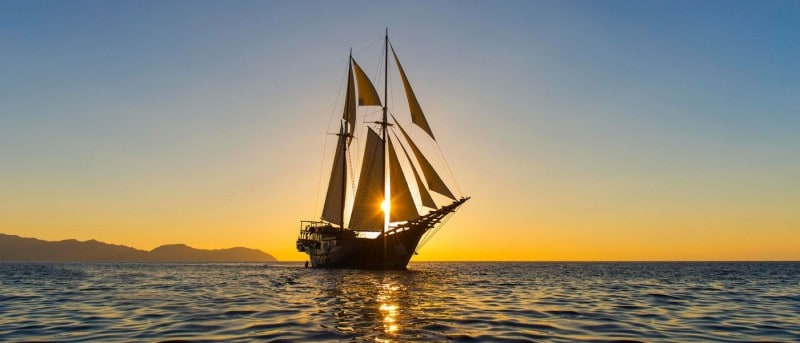 The Amandira with its masts up out at sea with the sun setting behind the boat
