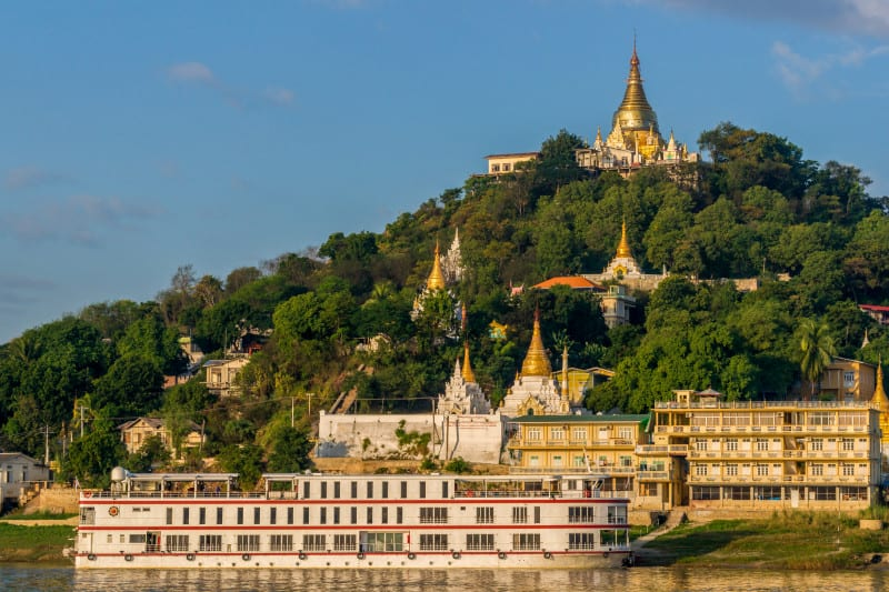 Sagaing, Myanmar - November 19: A cruise ship stops in front of a temple hill in the old capital Sagaing at sunrise. November 19, 2014 in Sagaing, Myanmar