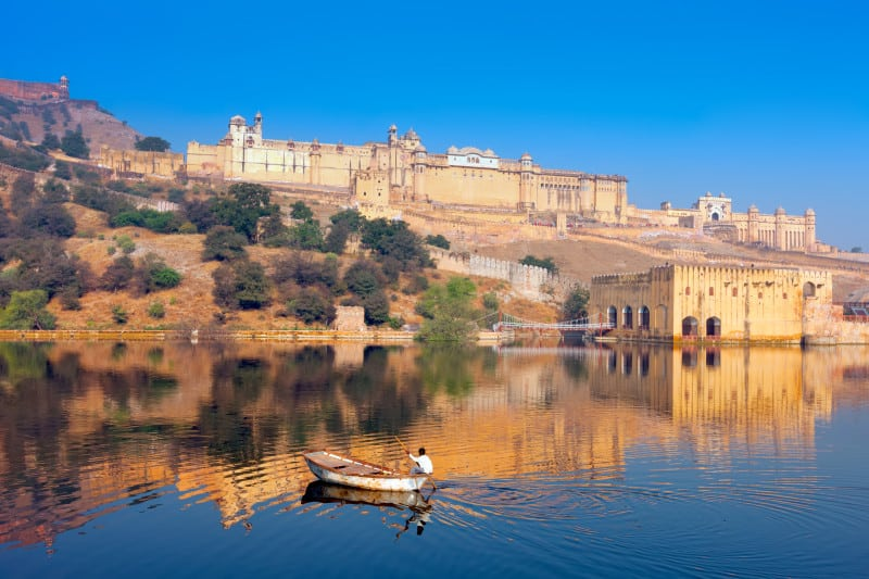 View of the Amber Fort with a lake and fisherman in the foreground and blue sky in the background