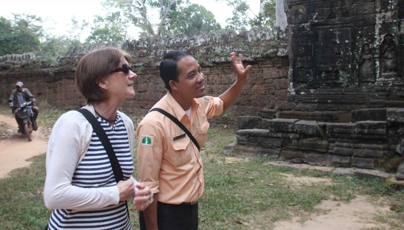 A guide talking to a traveller in cambodia whilst pointing at a monument