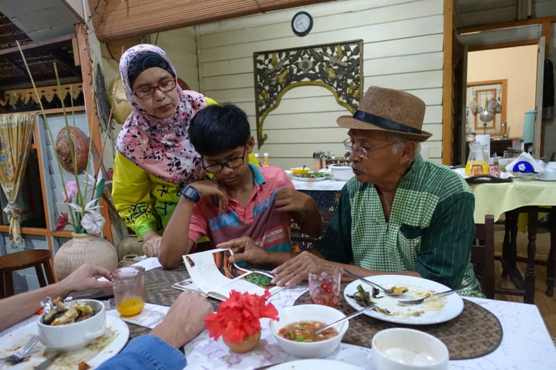 The owners of Suka Suka Homestay sat eating dinner