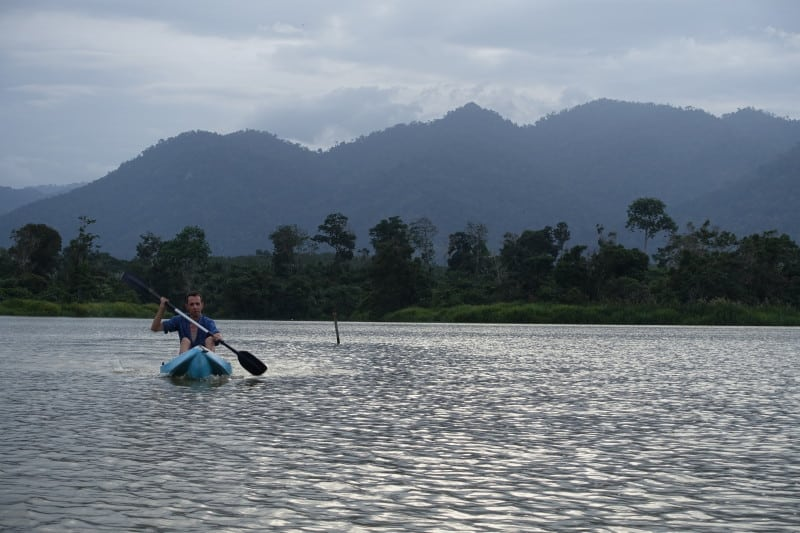 Traveller kayaking on Chenderoh Lake in Malaysia