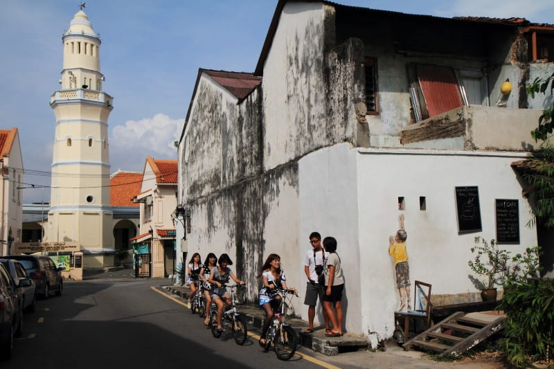 Tourists on Lebuh Cannon & Lebuh Acheh in George Town, Penang in front of Aceh Mosque