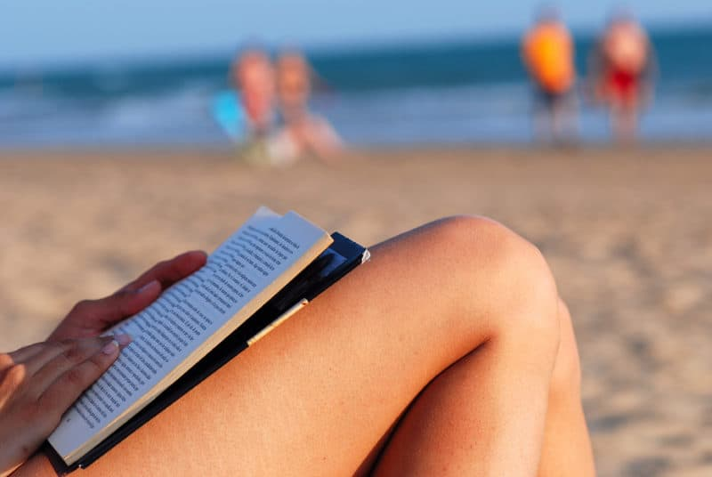 reading a book whilst in the sun on the beach