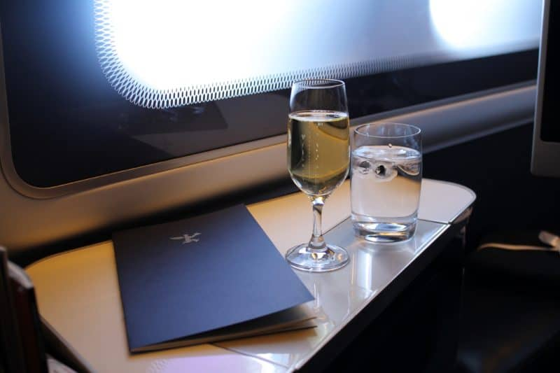 Champagne, a dark blue menu and a glass of water in a business class seat on a table next to the window