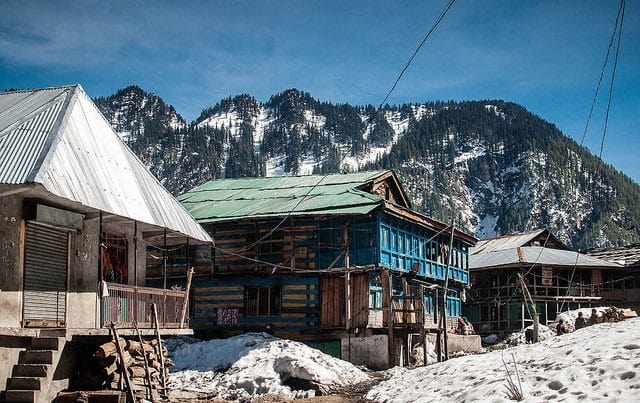 Malana Village in Himachal pradesh with forests, snow clad hills in the background