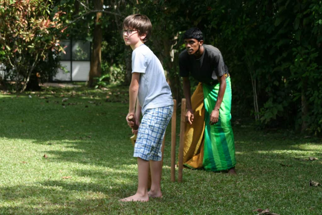 Child playing cricket with locals in Sri Lanka