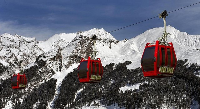 Solang valley ropeway with snow topped mountains in the background