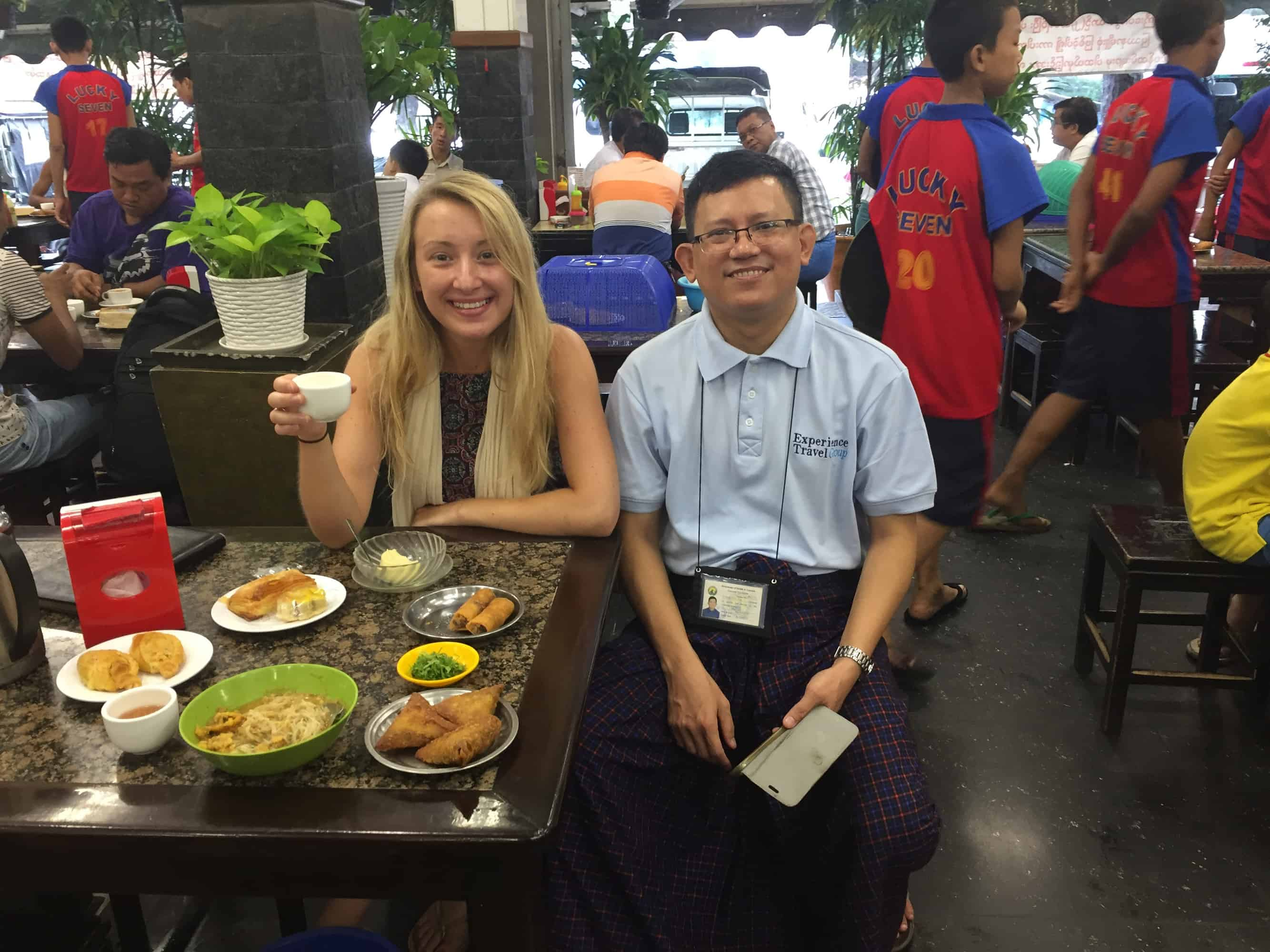 A guide and traveller sat together in a restaurant in myanmar