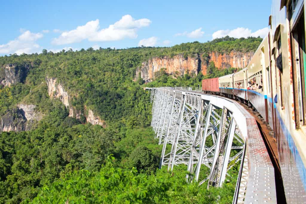 Train crossing the Goteik Viaduct in Myanmar with lush forests below