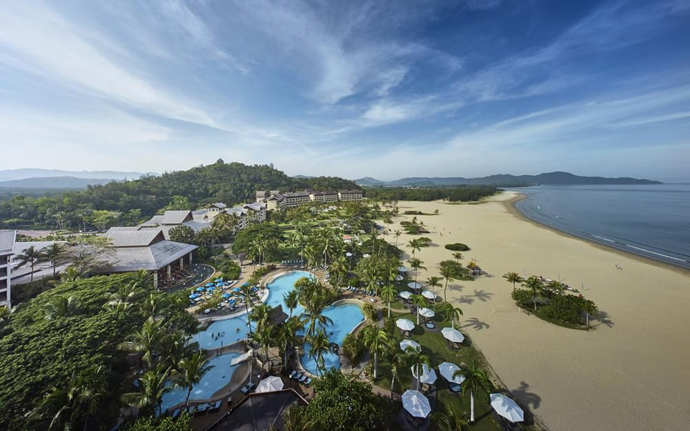 Birdseye view of the white sandy beach of Shangri La Rasa Ria and its swimming pools