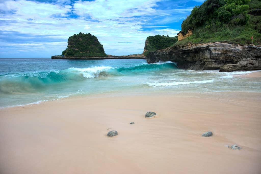Remote beach on Lombok with rocky outcrops heading into the ocean