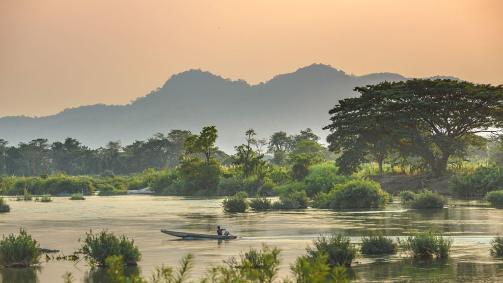 A fisherman floats along the mekong river around 4000 islands in Laos at dusk