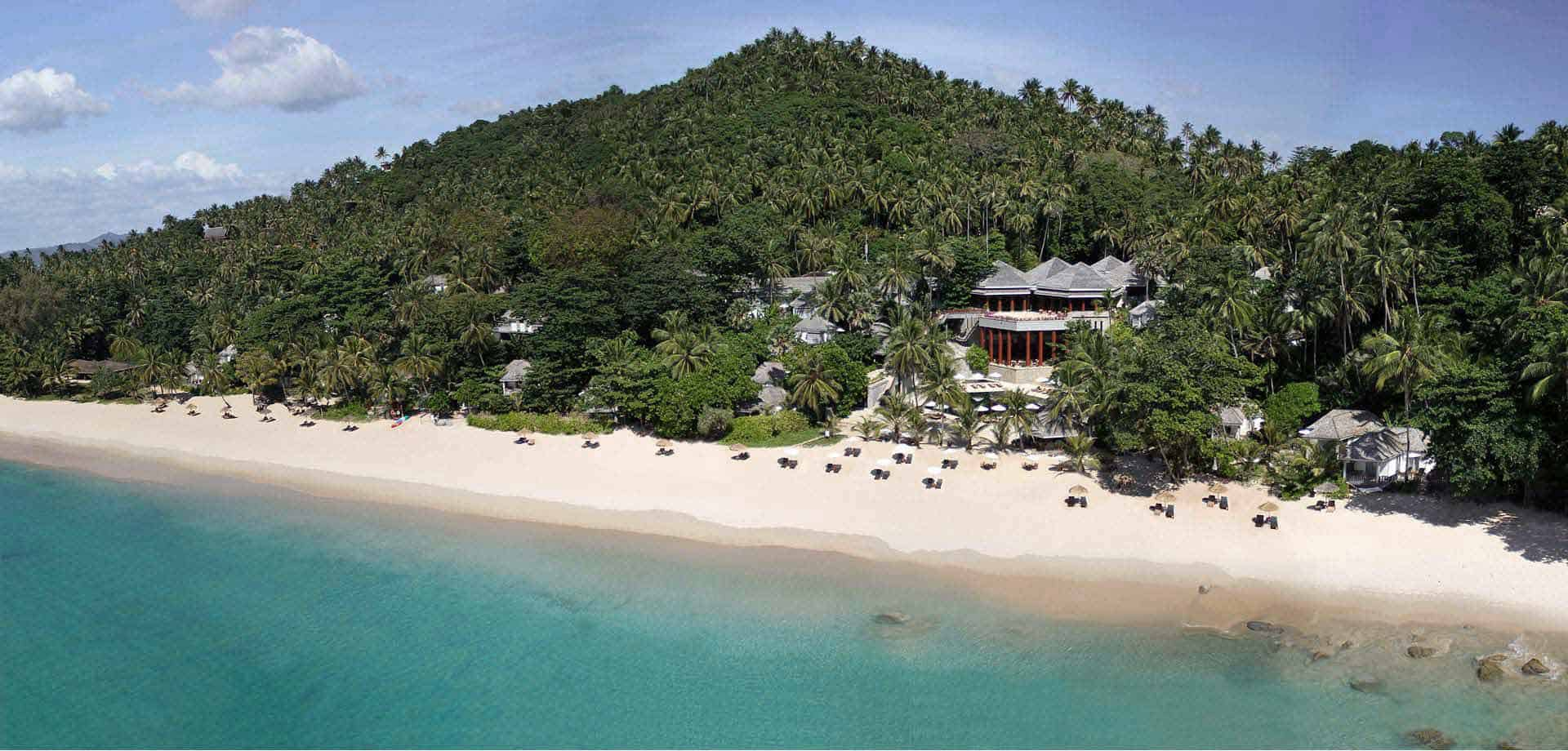 View from above of the beach of Surin Phuket. Clear blue sea, white sand beach and forest clad hill.