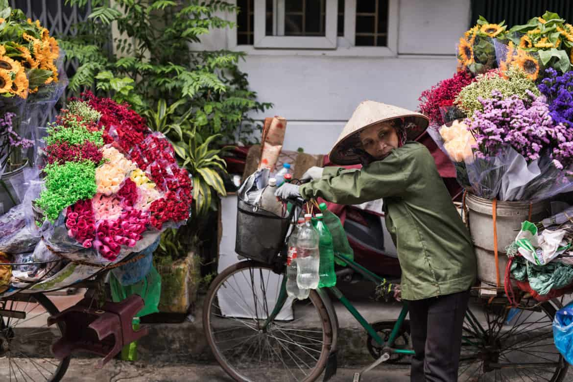 Flower hawker with conical hat pushing bike with flowers on the back