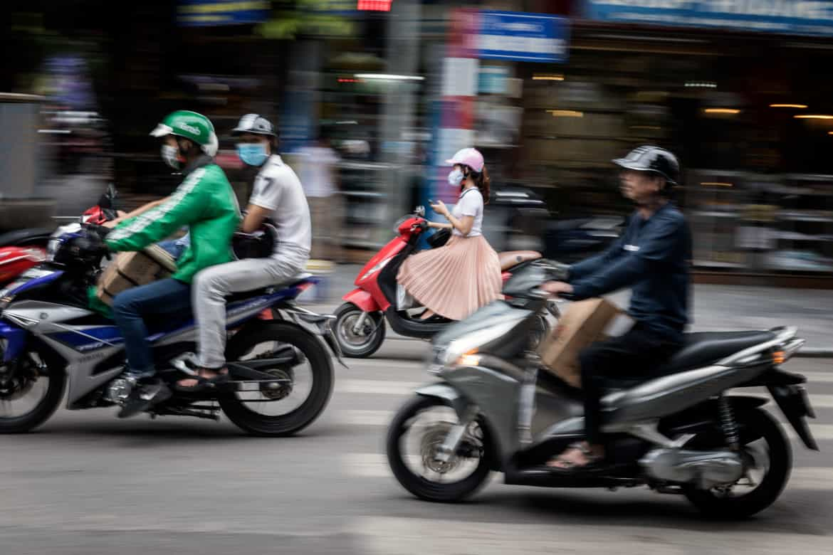Locals commuting on motorbikes in Ho Chi Minh City with shopfront blurred in the background