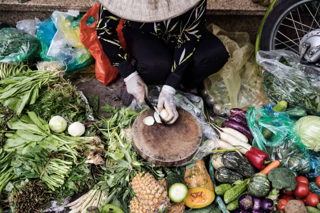 Hawker with conical hat in Hanoi cutting up fruit and vegetable