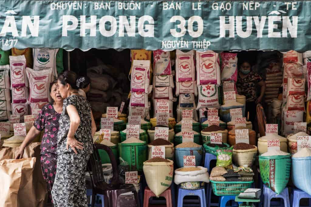 Shop front scene with awning hanging over spice being sold with two Vietnamese women talking in front