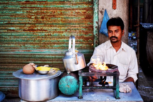 Chai Wallah staring at a lit flame on the side of a street in Mumbai