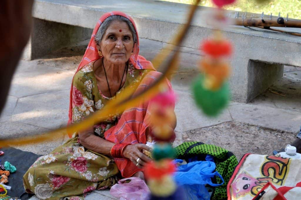 Local women dressed in a green sari and pink head covering with bindi on her forehead sat on a street