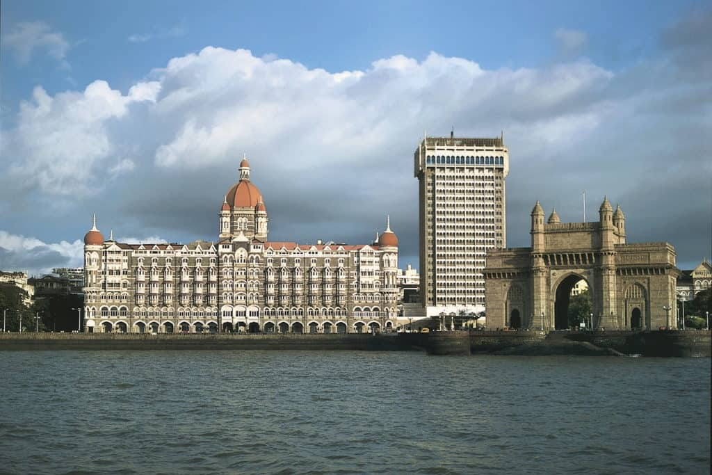 View of the Taj Mahal Palace Hotel from the sea. The Gateway to India stands to the left of the original building with the tower just behind it