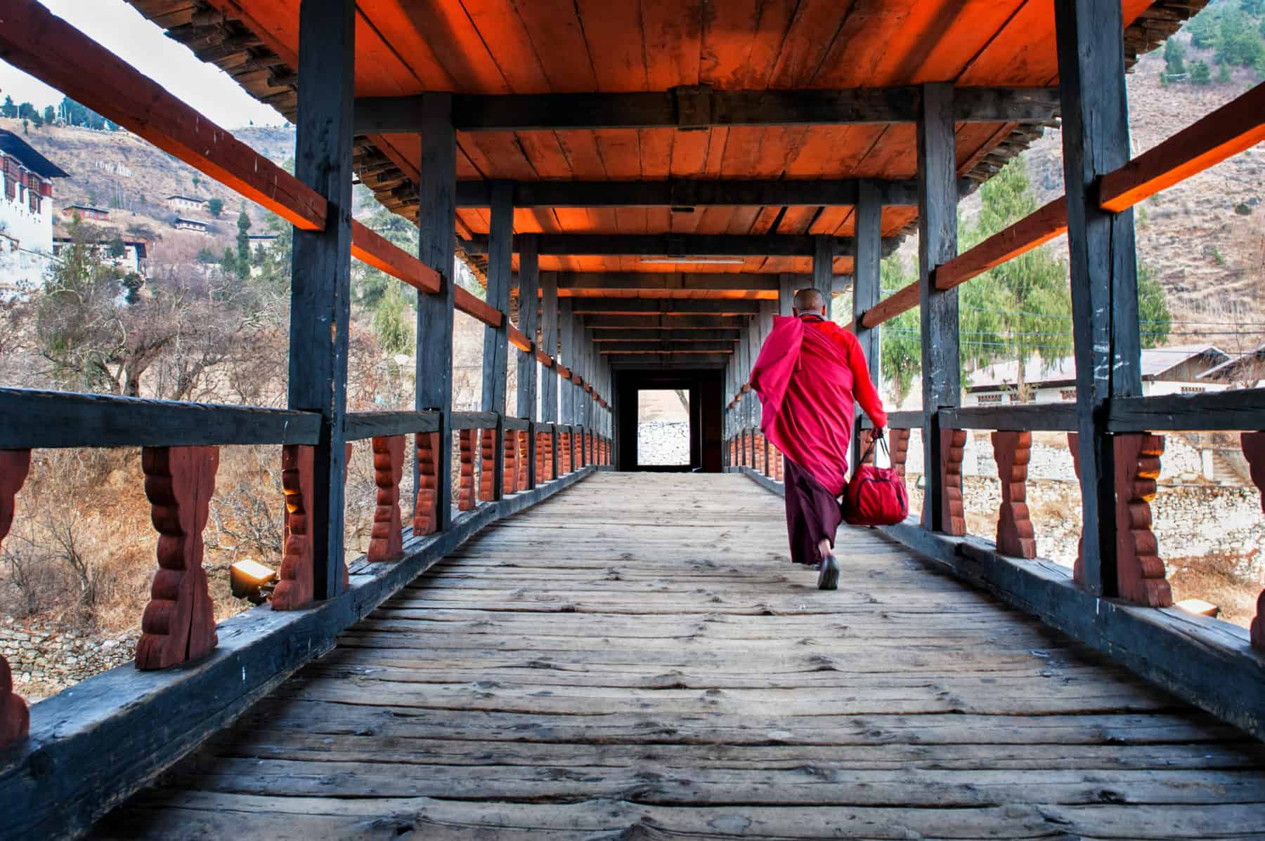A monks dressed in red traditional costume walks across a bridge in bhutan