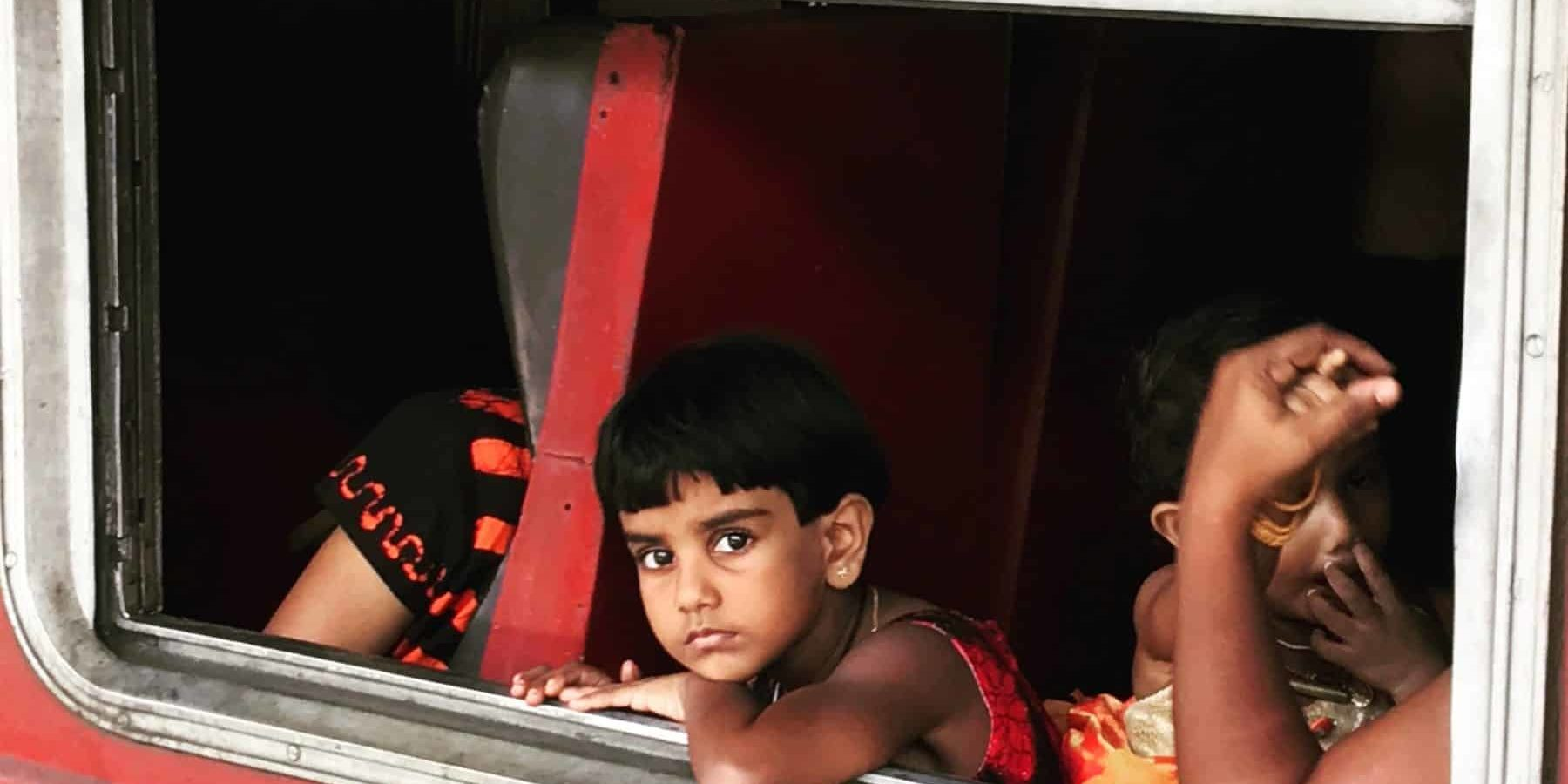 Child on train in India looking out of the window