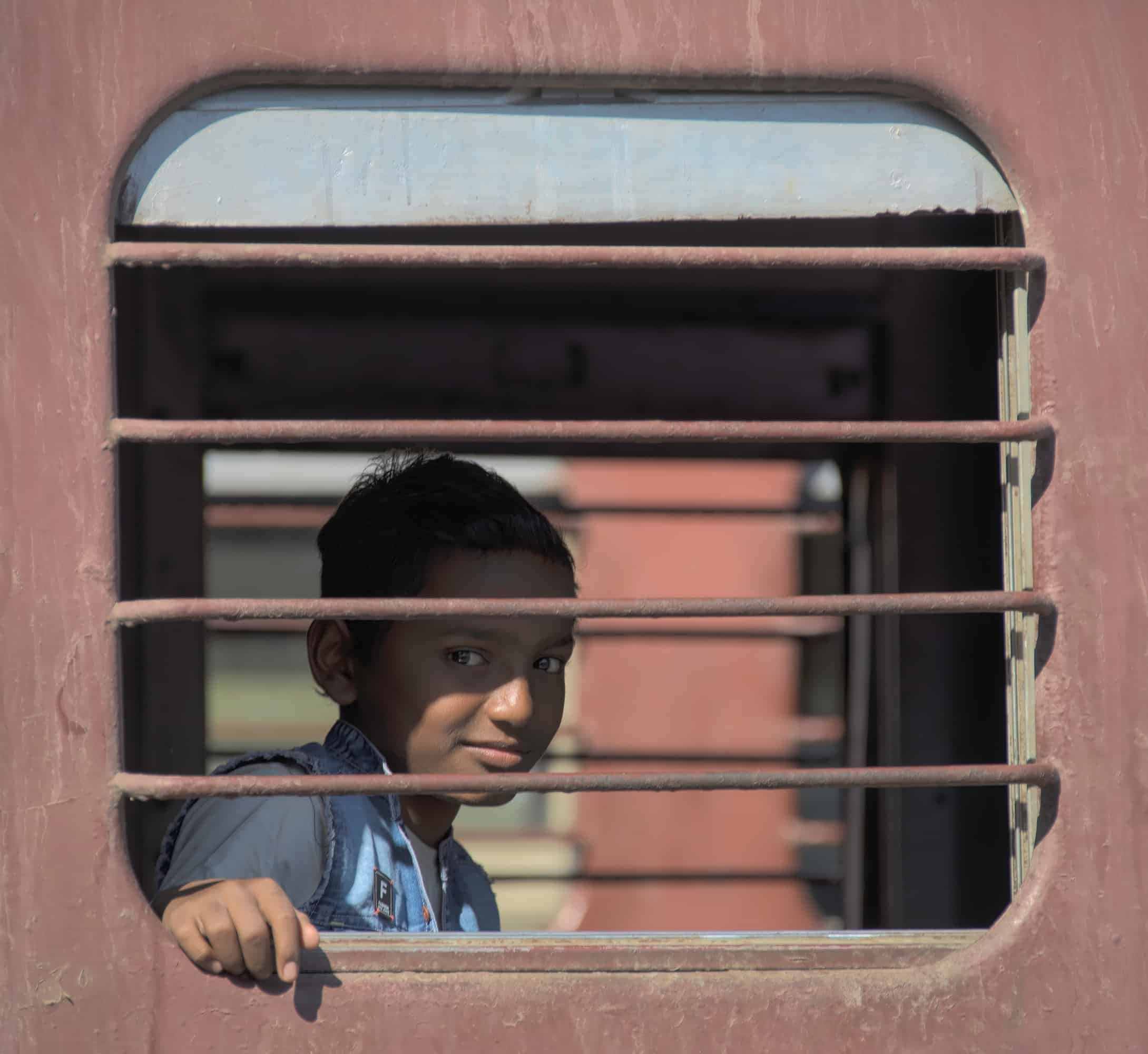 Boy on a train in India looking out of window