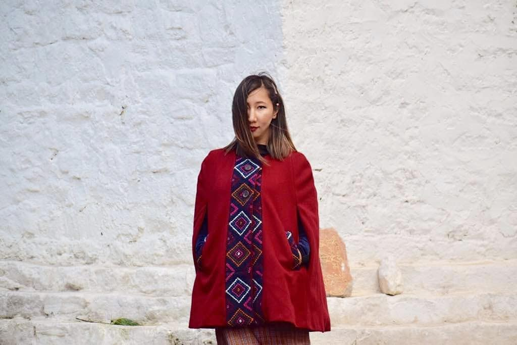 Geymit wearing a She Bhutan maroon cape yathra jacket