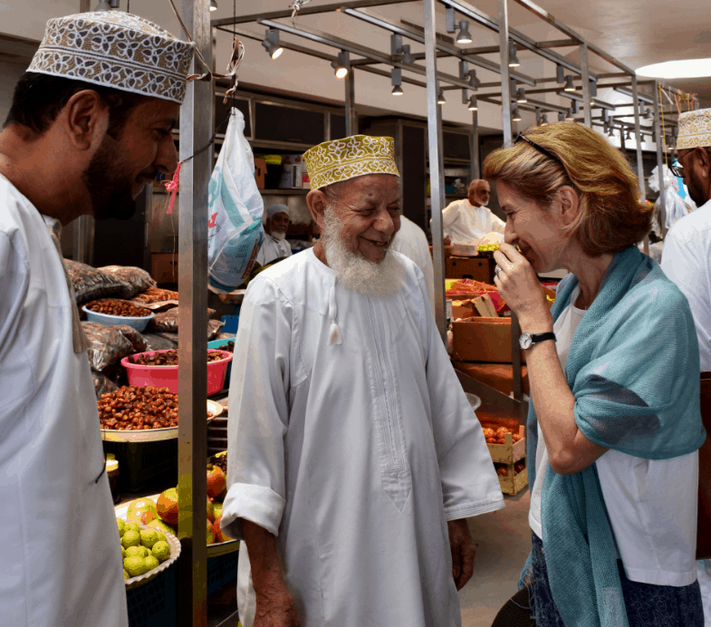 Traveller laughing with guide in Oman market