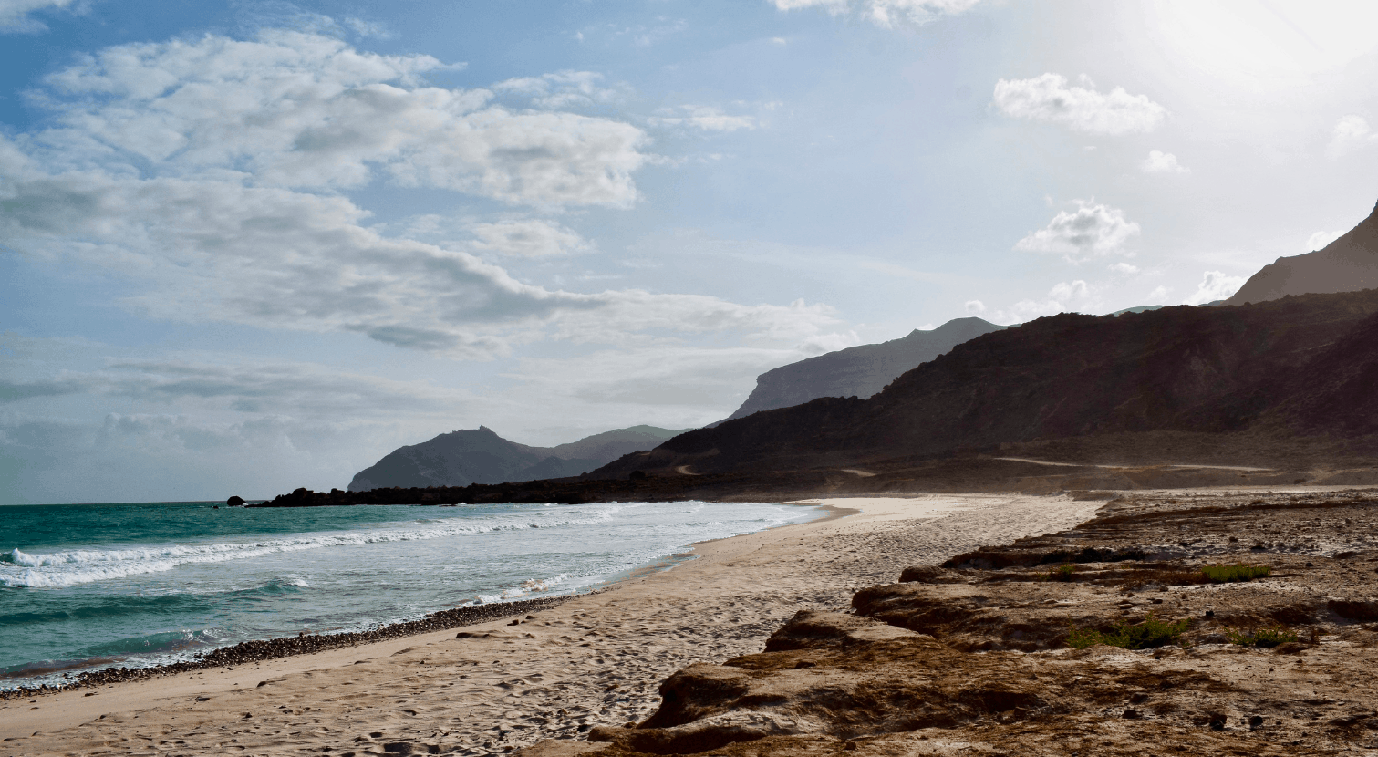Beautiful beach in Oman with ocean and waves and mountains in the background