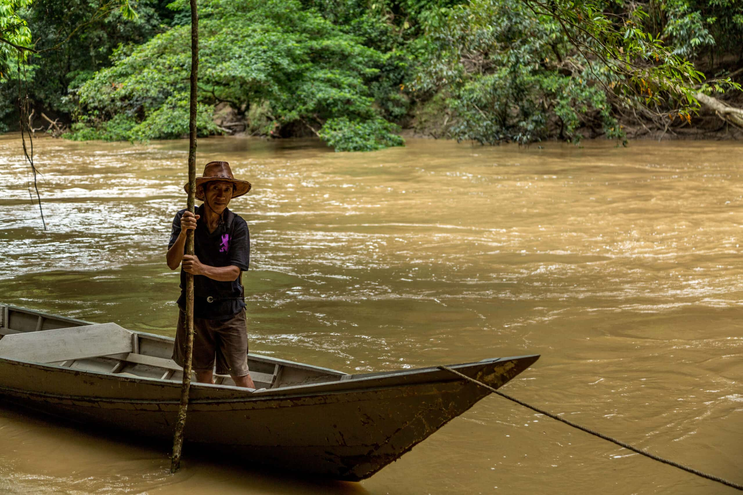 Man standing in wooden boat in the Kinabatangan River with jungle backdrop in Borneo