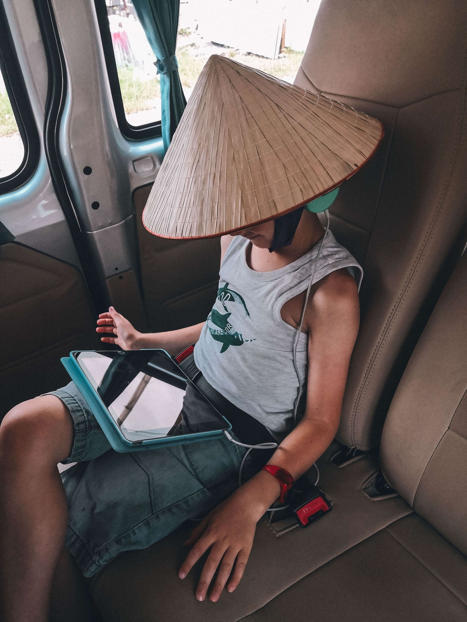 Child wearing traditional vietnamese conical hat whilst on his tablet