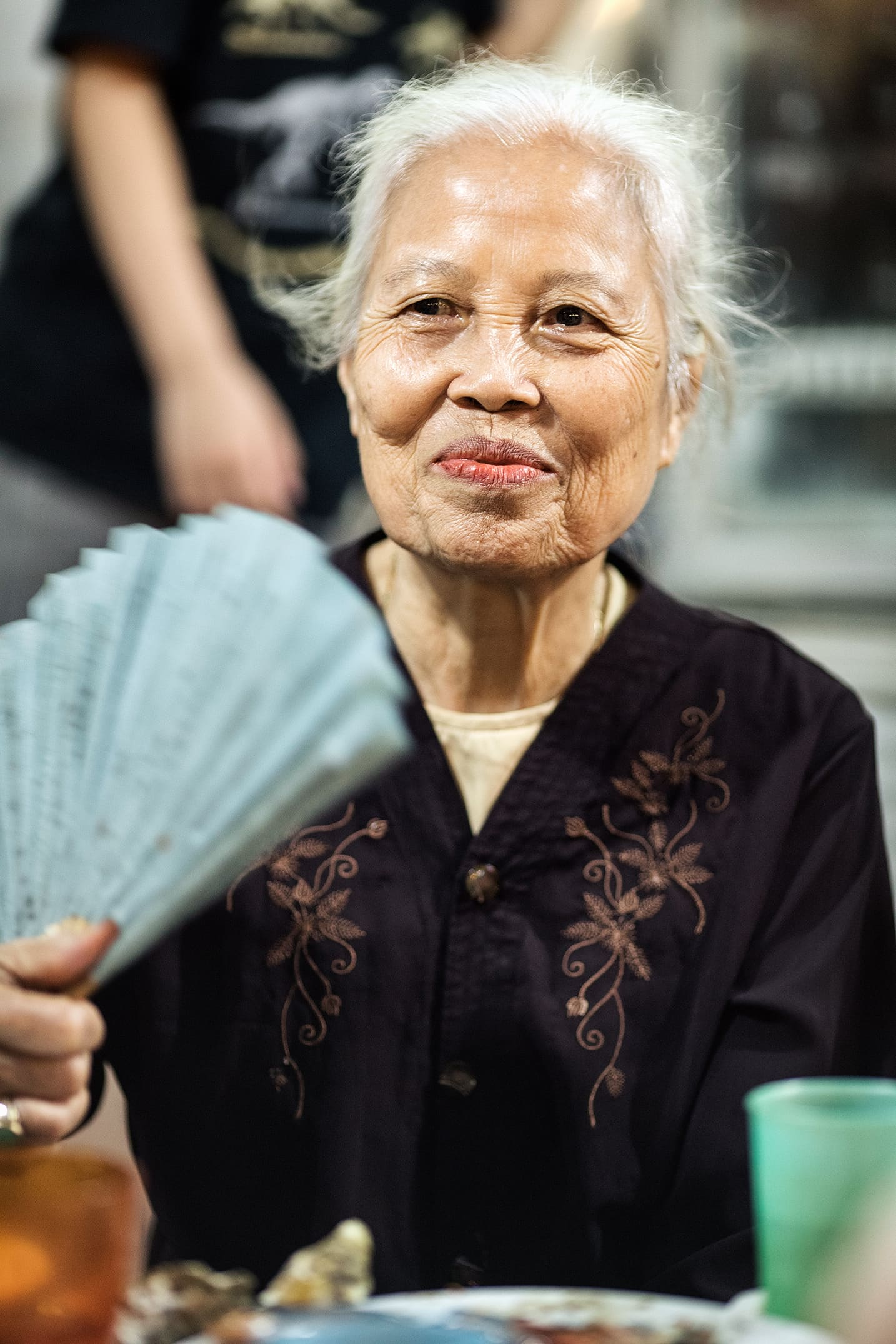 Old local woman eating Street food in Hanoi in the evening