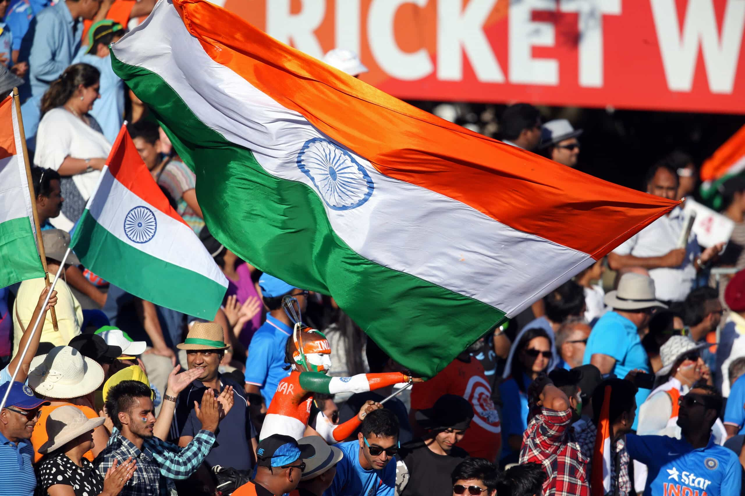 Indian cricket fans celebrating and flying a huge flag of India