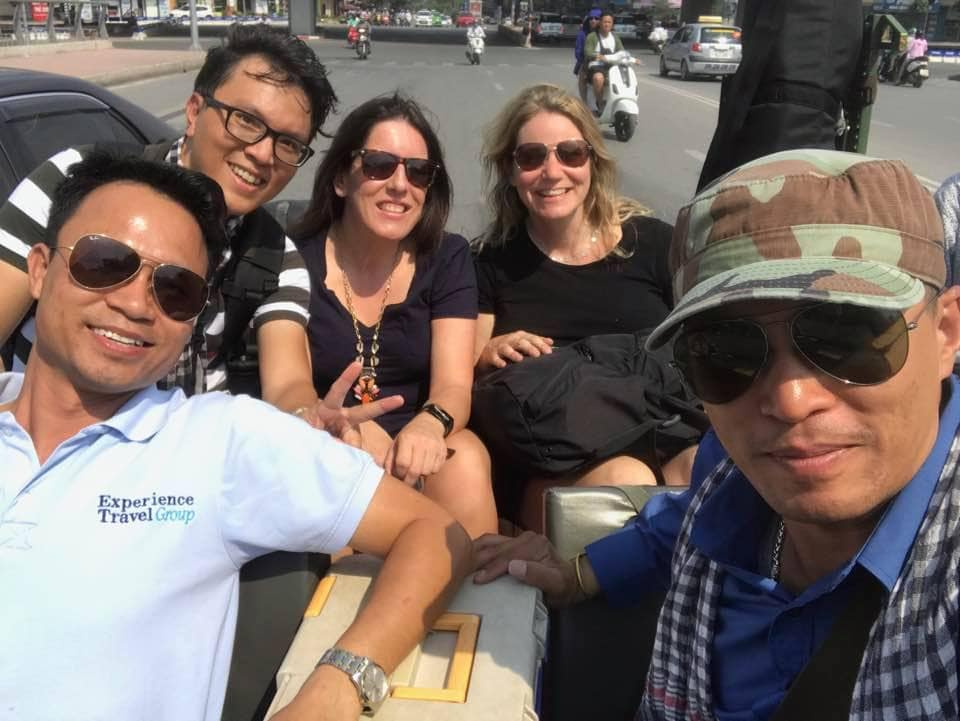 Guides and travellers in the back of an open top vehicle having fun in Vietnam