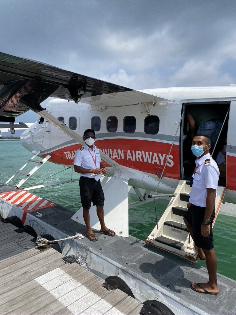 Travel on a seaplane in the Maldives with staff wearing covid face masks