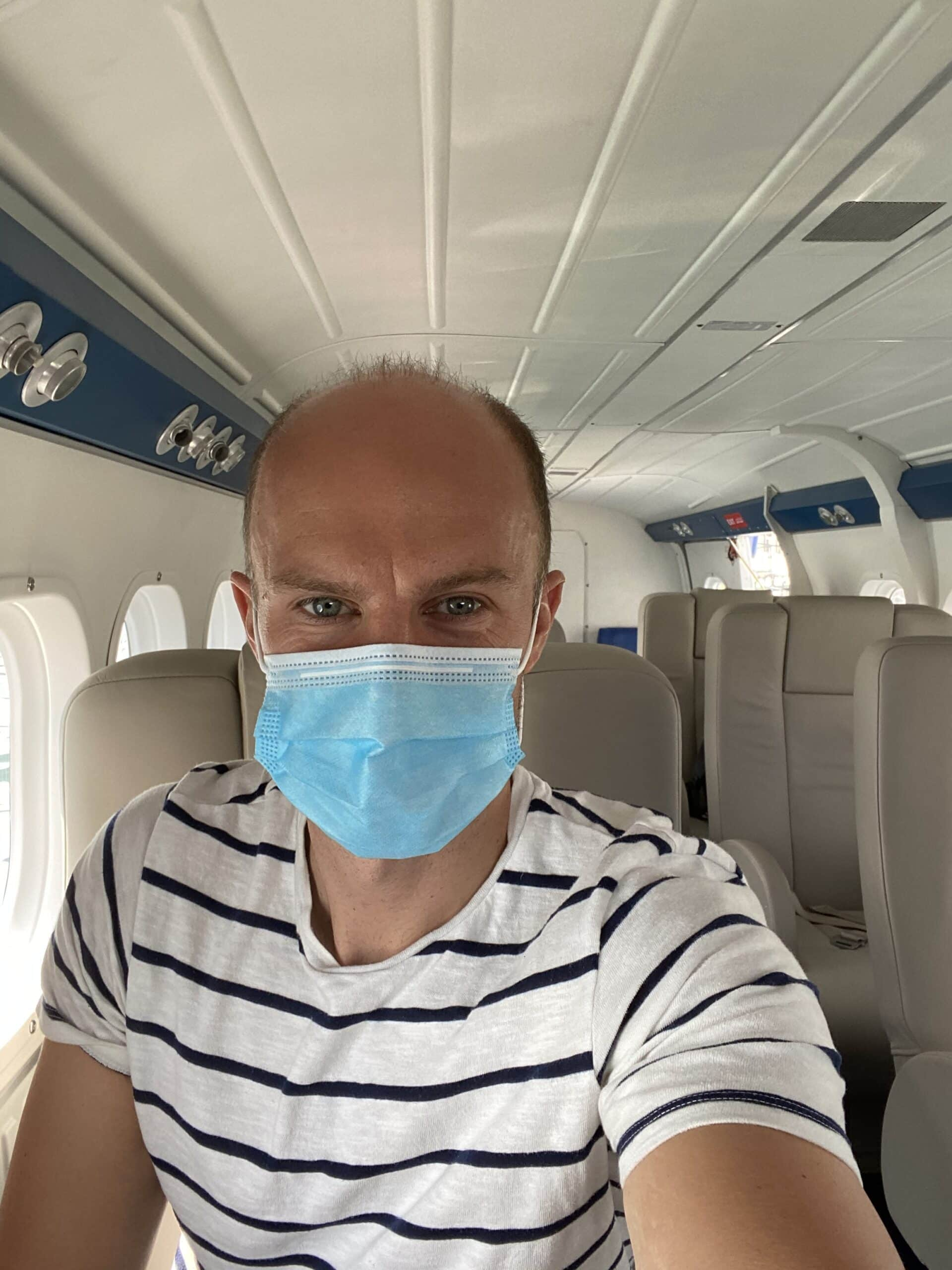 Tourist wearing a mask on a seaplane to The Maldives