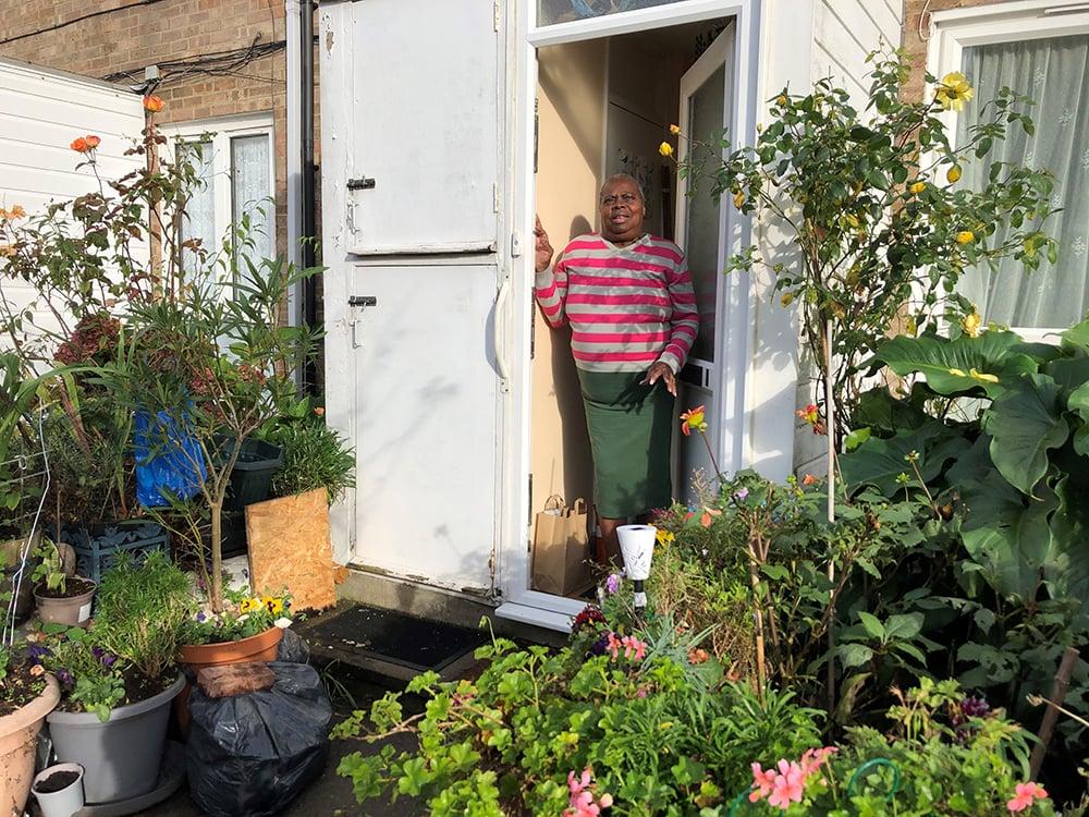 Woman standing at doorway in garden