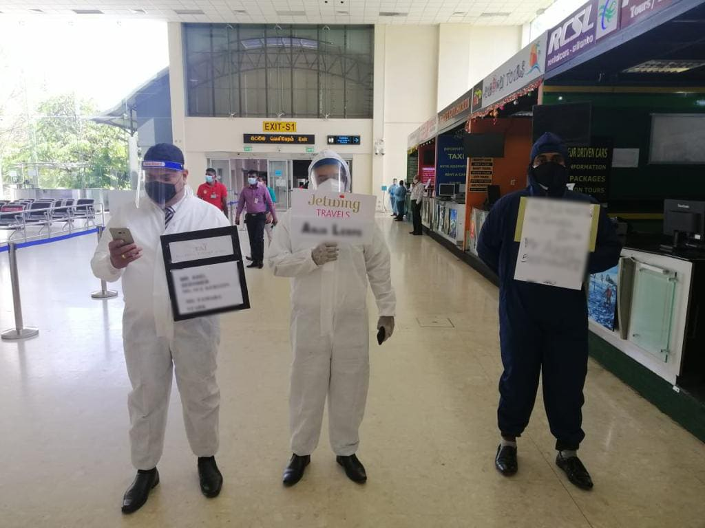 Guides wearing hazmat suits in the arrivals of Colombo airport in Sri Lanka