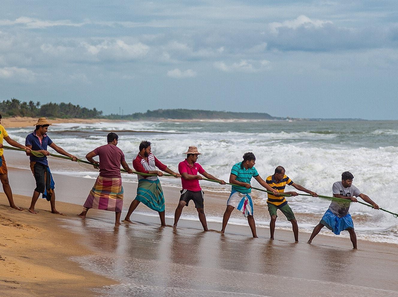 Men hauling in fish on Sri Lankan beach at Ravana Garden hotel