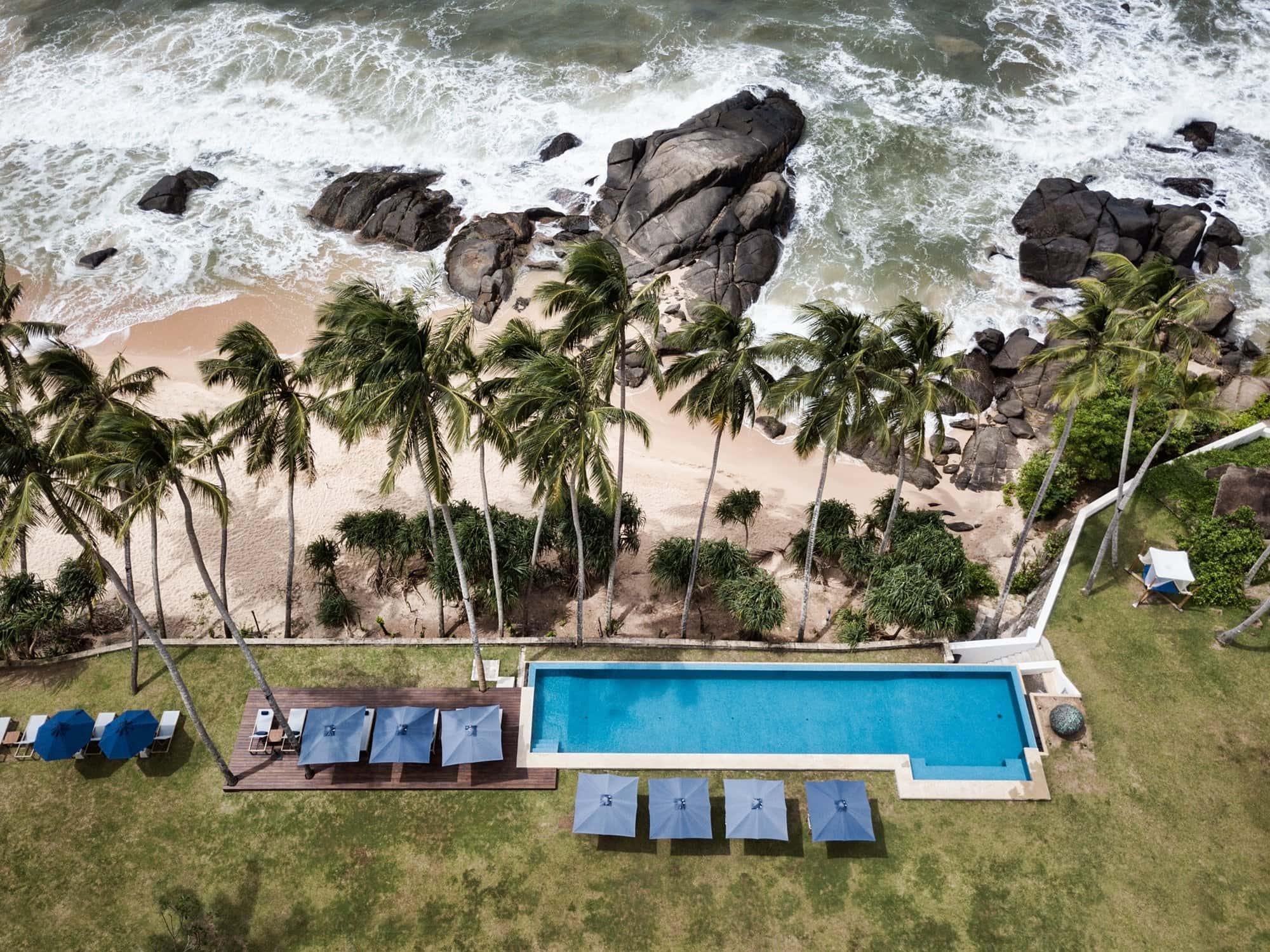 Aerial shot of Kumu Beach swimming pool with palm trees and rocky beach